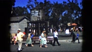 1963: parents and their young children walk around in public area near building. Stock Footage