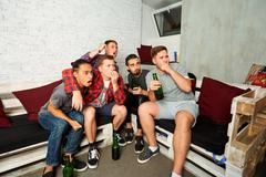 Friends emotionally watching football on TV. Fans drink beer and relax togeth Stock Photos