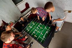 Friends guys together to play board games, table football. Output students. R Stock Photos
