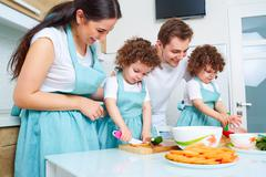 Daughters twins, dad and mom cook in the kitchen. A happy family. Parents tea Stock Photos