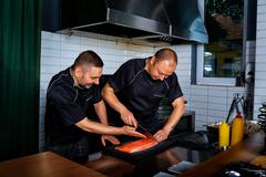 Two men cook chef cut up, cooked fish in restaurant commercial kitchen. Kuvituskuvat