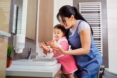 Mother and daughter washing their hands in the bathroom. Care and concern for Stock Photos