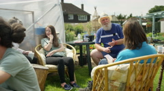 4K Cheerful group relaxing & chatting with drinks in shared community garden Stock Footage