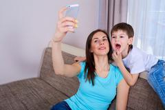 Happy young mother is making selfie photo with her son. The boy growing teeth Stock Photos
