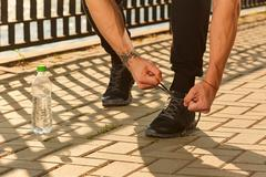 Tying sports shoe.Running and sport concept.Athlete,  tying sport footwear la Stock Photos