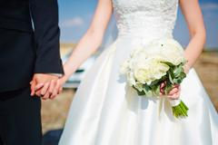Bride hold groom by the hand and wedding bouquet. Focus on wedding flower bou Stock Photos