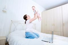 Mother and baby in bed.Child and parent together at home.Young mom playing wi Stock Photos