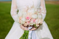 Beautiful wedding bouquet of flowers in hands of the bride. Stock Photos