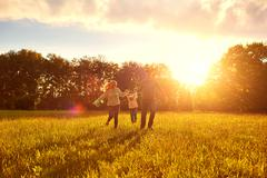 Happy family playing on the grass in the park in the evening. Stock Photos