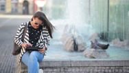 Beautiful Girl reading and browsing an ebook or a tablet sitting in a bench at Stock Footage