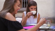 Two young women are sitting at café restaurant. They're talking and laughing Stock Footage
