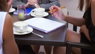 Three young women are learning and talking at the outdoor cafe restaurant. Stock Footage