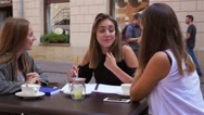Three young women are done with learning. Outdoor café background Stock Footage