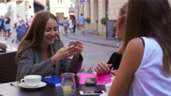 Three young women are sitting and talking while using mobile phone Stock Footage