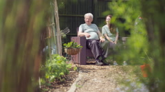 4K Volunteer working in community garden with man & woman relaxing in background Stock Footage