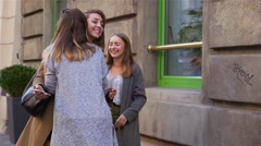 Two young women are meeting a female friend on the street. City background Stock Footage