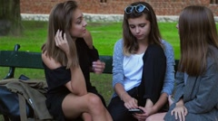 Three young women are sitting on the bench and comforting one of them Stock Footage