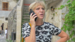 Serious blonde woman of middle age  talks on the phone Stock Footage