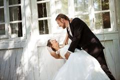 Young beautiful dressy newlyweds smiling, dancing outdoors Stock Photos