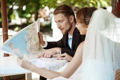 Young beautiful newlyweds smiling, choosing honeymoon trip, looking at map Stock Photos