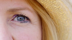 4K Extreme close up on the eye of attractive mature woman wearing a straw hat Stock Footage