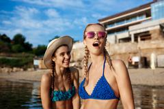 Young beautiful girls in swimwear rejoicing, smiling, laughing at seashore Stock Photos