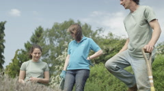 4K Gardeners working together in community allotment, man digging up the soil Stock Footage