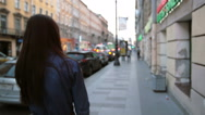 Backview of a girl at the street, flipping her hair back. Blurred background Stock Footage