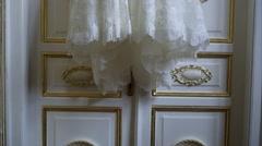 Bride wedding dress hanging on the door Stock Footage
