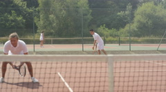 4K Male doubles tennis players serving & scoring a point on outdoor court Stock Footage