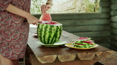 Ripe watermelon. Female hands cutting the watermelon into thin slices. HD Stock Footage