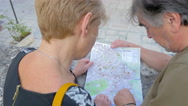 Tourist couple' s back consulting the map of the city Stock Footage