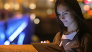 A beautiful brunette woman, using her tablet. Night city, blurred lights on the Stock Footage