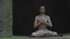 Young man practicing fitness yoga exercises in a cave. Stock Footage