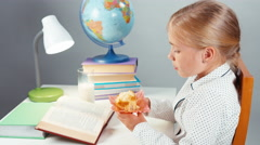 Portrait school girl 7-8 years reading book drinking milk and eating muffin Stock Footage