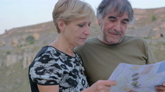 happy couple of  tourists observe the map and chat pleasantly Stock Footage