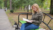 Blonde Woman Reading Book on Brench in Autumn Park. Stock Footage