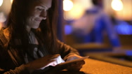 A pretty young woman using her tablet at night. She smiles, touches her hair Stock Footage