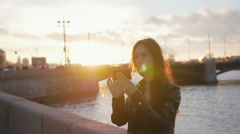 A girl taking selfie as the sun sets in a wonderful place. Busy road, a bridge Stock Footage
