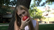 Pretty young Blonde Girl eating a juicy red Apple in the Park Stock Footage