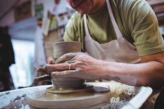 Cropped image of potter molding shape while sitting at workshop Stock Photos