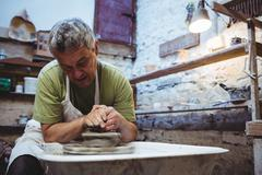Concentrated craftsman making ceramic container in pottery workshop Stock Photos