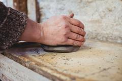 Cropped image of man molding clay at workshop Stock Photos