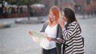 Two young attractive girls are looking aside in the urban zone while exploring Stock Footage