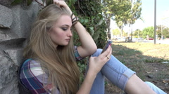 Angry upset Girl chating with Mobile Sell Phone sitting on the Ground Stock Footage
