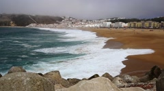 Large ocean waves on Atlantic cost beach in Nazare, Portugal during misty day Stock Footage