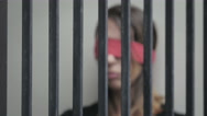 Abused young woman imprisoned in a cell, blindfoldedwith red ribbon Stock Footage