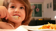 Little girl eating spaghetti with tomato sauce Stock Footage