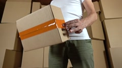 Warehouse worker twisting a small parcel in his hands. Super slow motion shot Stock Footage