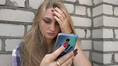 Angry upset Girl chating with Mobile Sell Phone standing by the Wall Stock Footage
